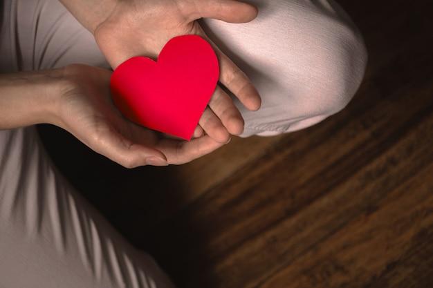 붉은 마음을 주는 손. 사랑을 주는 개념입니다. 의료, 생명 보험, 정신 건강 배너입니다. 검정색 배경, 복사 공간이 있는 배너 photo