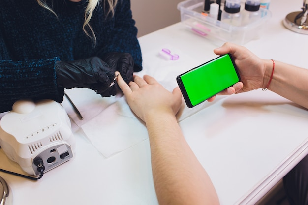 Hands in gloves cares about man's hand nails. manicure beauty salon. smartphone, green screen, hromakey