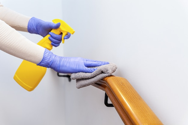 Hands in gloves cleaning stairs railings with rag