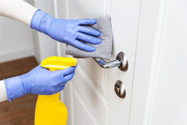 Hands in gloves disinfecting door handle with rag and spray detergent