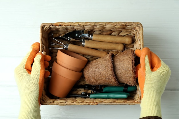Hands in gloves hold basket with gardening tools, top view