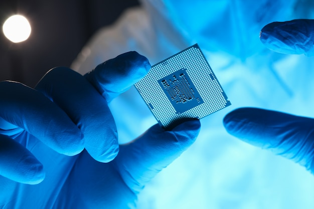 Hands in gloves hold chip testing microelectronics