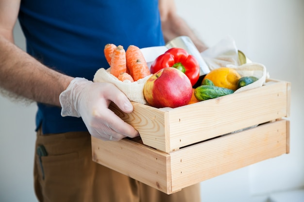 Hands in gloves holding food box