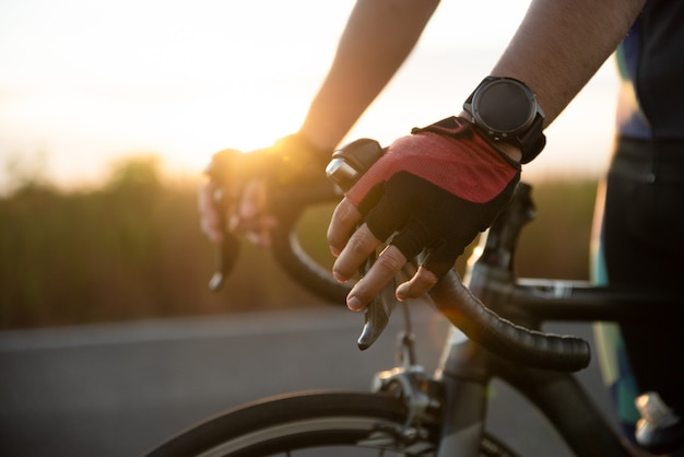 Hands in gloves holding road bicycle handlebar