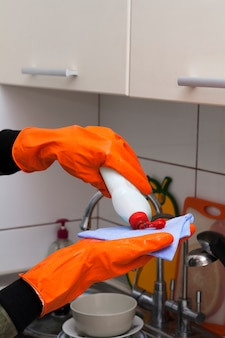Hands in gloves pour washing liquid in the kitchen