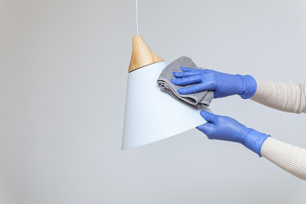 Hands in gloves removing dust cleaning electric lamp chandelier Premium Photo
