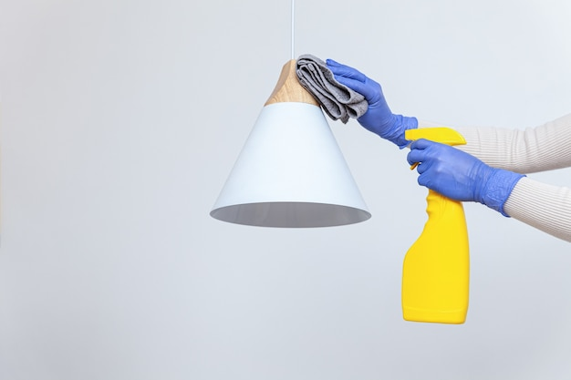 Hands in gloves removing dust cleaning electric lamp chandelier
