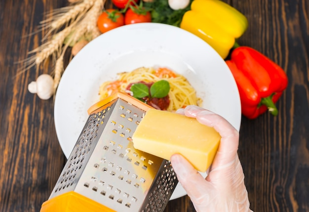 Hands in gloves rub cheese on a grater