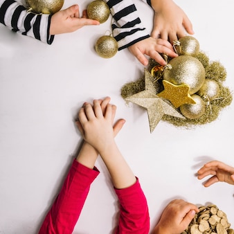 Hands and golden christmas ornaments