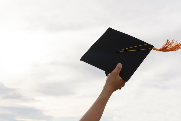 The hands of the graduates hold a black hat and a yellow tassel extends to the sky.