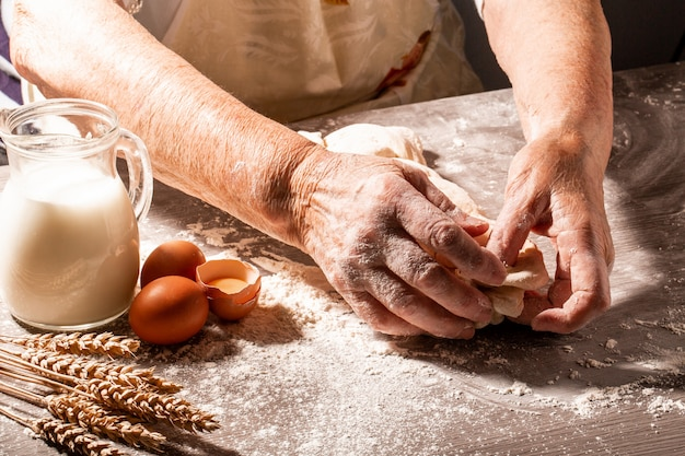 Hands of granny kneads dough. 80 years old woman hands kneading dough. homemade baking. pastry and cookery