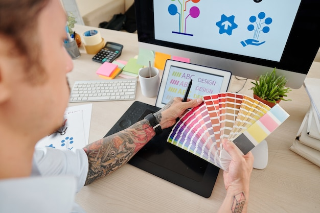 Hands of graphic designer looking at palette and choosing color for company logog