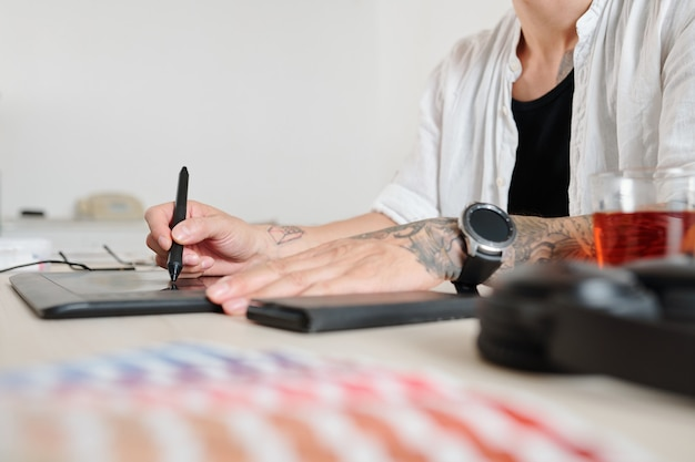 Hands of graphic designer using on graphic tablet when drawing logotype for client