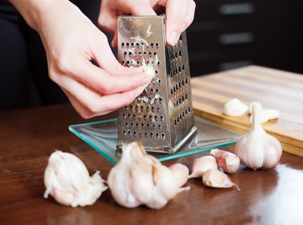Hands  grating garlic with grater