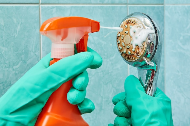 Hands in green rubber protective gloves wash head of shower with help of cleaning spray.