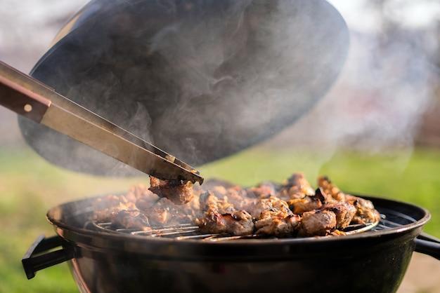 裏庭の屋外グリルでバーベキュー肉を焼く手。