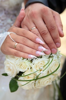 Hands of the groom and the bride with wedding rings hold a wedding bouquet from white roses close up