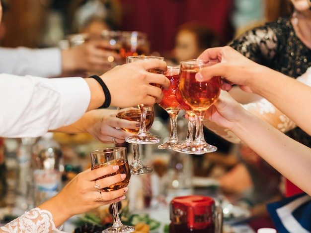 Hands of a group of people clinking and toasting glasses of red wine at a festive party in a restaurant