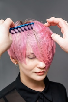 Hands of hairdresser are combing short pink hair.