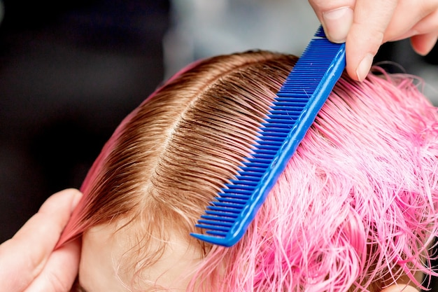 Hands hairdresser combs pink hair of young woman close up in hair salon.