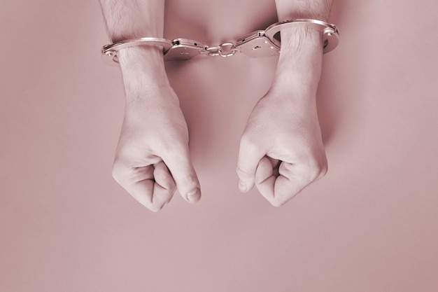Hands in handcuffs, copy space. imprisonment concept. deprivation of liberty and apprehend perpetrators. fists.