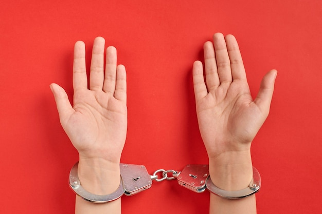 Hands in handcuffs on red background. palms up. life imprisonment concept. deprivation of liberty and catch perpetrators.