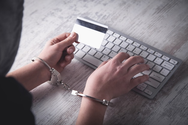 Hands in handcuffs typing on keyboard. cyber crime concept