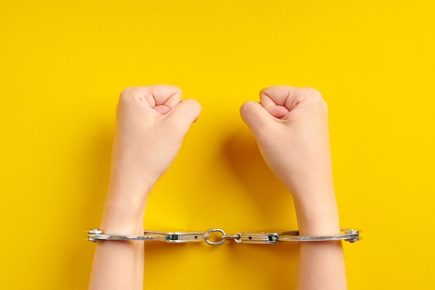 Hands in handcuffs on yellow background. imprisonment concept. deprivation of liberty and apprehend perpetrators. fists.