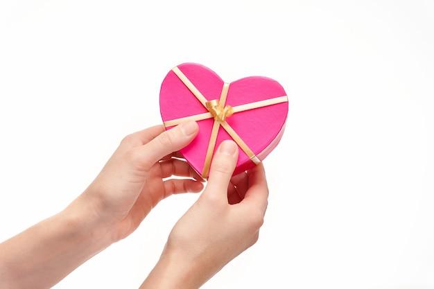 Руки, вручая подарок в форме сердца на белом фоне, копией пространства