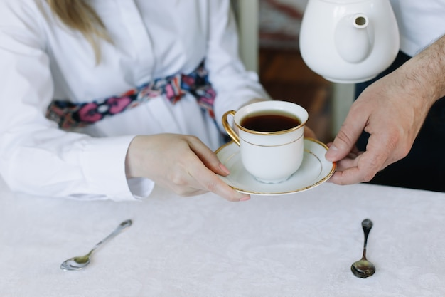 Hands of happy couple drinking hot tea at home
