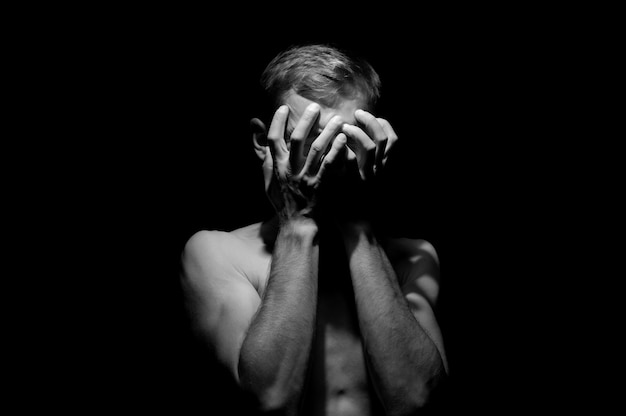 Hands on head, black and white dramatic photo of a man