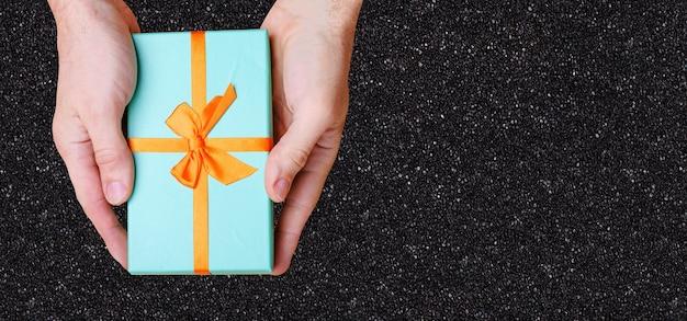 手は黒い壁にオレンジ色の弓が付いた青い箱を持っています。上からの眺め。高品質の写真