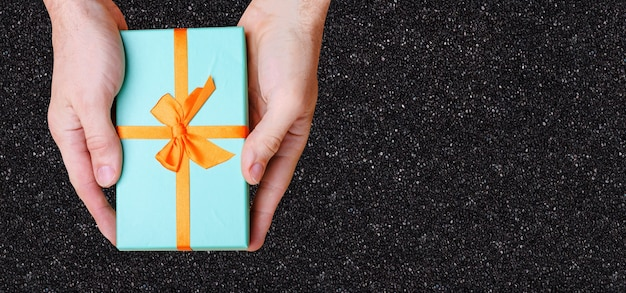 手は黒い壁にオレンジ色の弓で青い箱を持っています。上からの眺め。高品質の写真