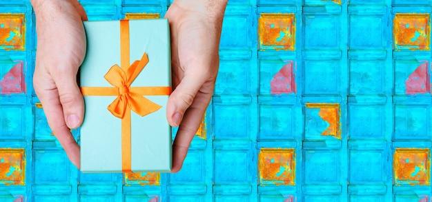手は青い壁にオレンジ色の弓で青い箱を持っています。上からの眺め。高品質の写真