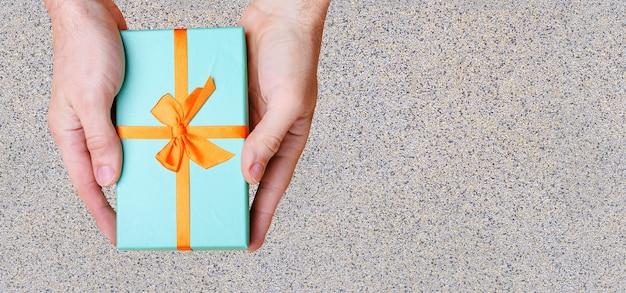 Руки держат у стены ящик синего цвета с оранжевым бантом. вид сверху. фото высокого качества
