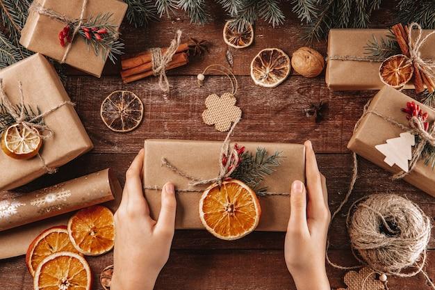 手はクラフト紙と天然素材で包まれたクリスマスプレゼントを持っています