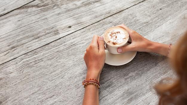 手は一杯のコーヒーを持っています。