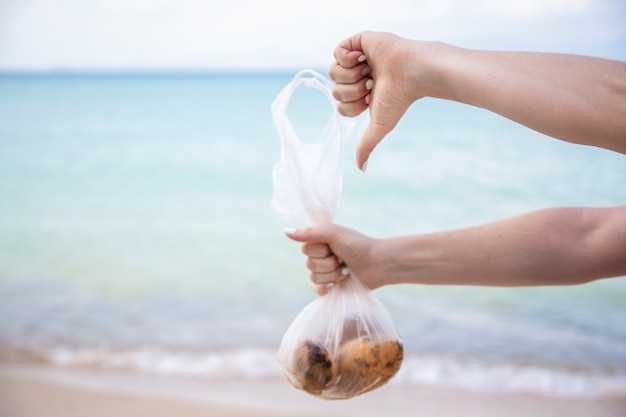 손은 과일이 든 비닐 봉지를 들고 오염에 대한 얼굴 개념이 없는 바다에서 엄지손가락을 보여줍니다.