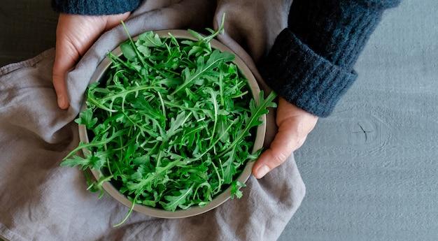 Руки держат тарелку со свежей зеленой рукколой на сером фоне, концепция tidewater green color.