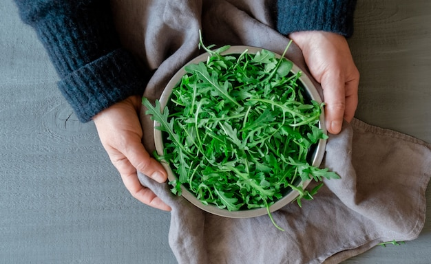 Руки держат тарелку со свежей зеленой рукколой на серой поверхности, концепция tidewater green color.