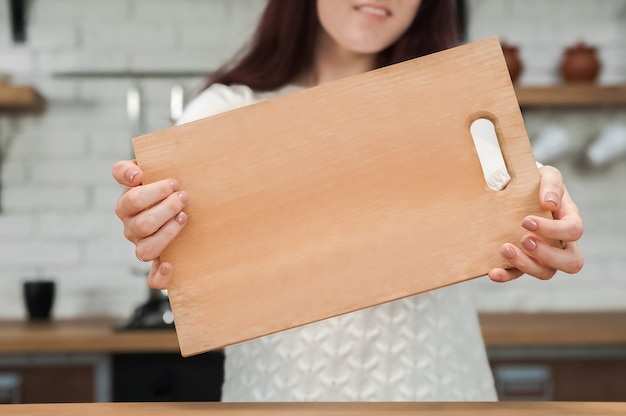 Hands hold board against background rustic kitchen and copy space.