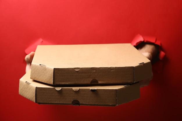 Руки держат коробки с вкусной пиццей на красном
