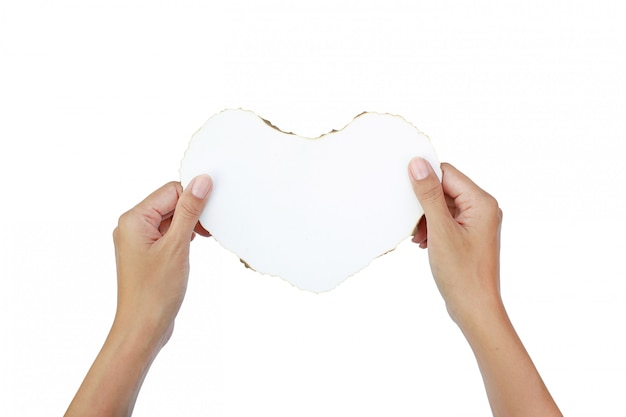Hands hold burning paper heart on white background.