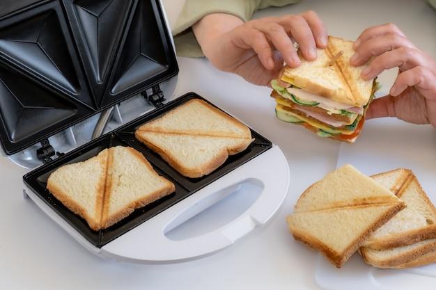 손을 잡고 흰색 테이블에 토스터 근처 치즈, 베이컨, 야채와 함께 조리 된 신선한 샌드위치.