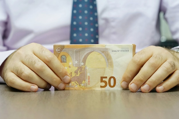 Hands hold and counting euro banknotes
