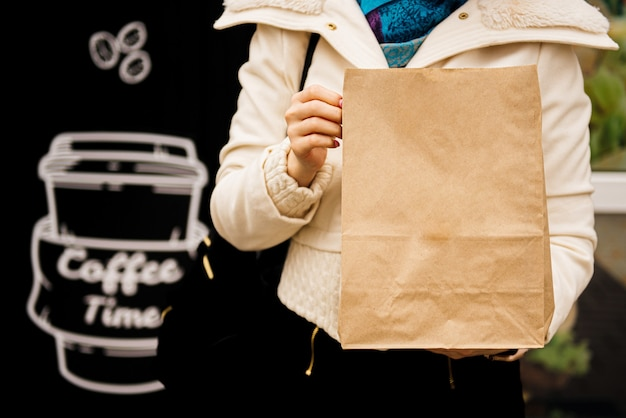 Hands  hold a craft bag with food and a paper cup with coffee or tea. takeaway food concept