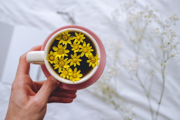 Hands hold cup with yellow flowers inside, on a white bed in the morning. spring background