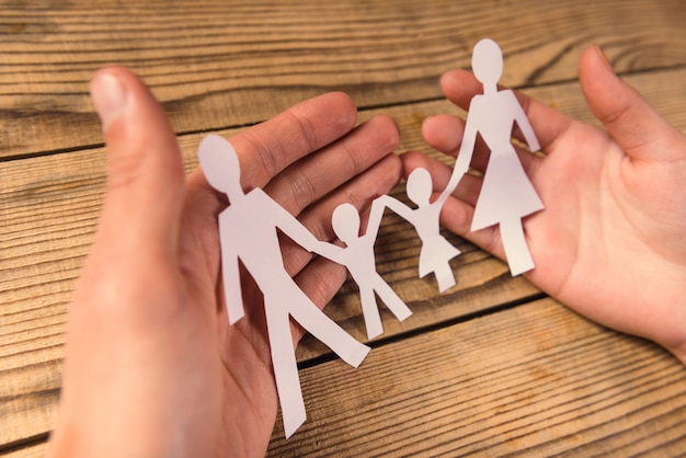 Hands hold a family of paper on wooden table.