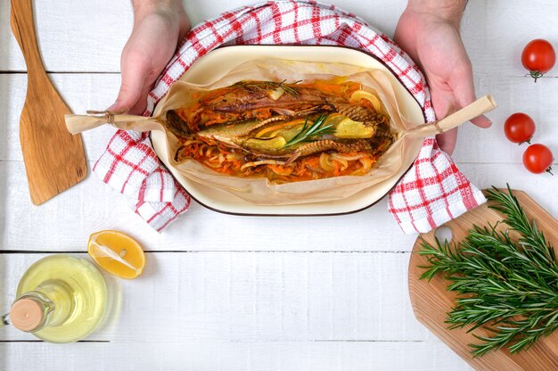 手は作りたての魚を持っています。白い木製のテーブルに野菜、芳香性のハーブ、オリーブオイル。上面図