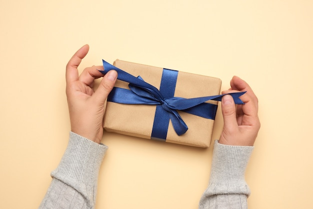 Hands hold a gift paper box on a beige background